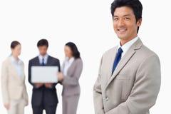 Homem de negócios com colegas e portátil atrás dele Imagem de Stock