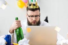 homem de negócios com a coroa de papel na cabeça e na garrafa do champanhe à disposição que olham a tela do portátil fotografia de stock