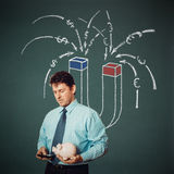 Homem de negócios com da calculadora, do mealheiro e do dinheiro do ímã parte traseira sobre Fotografia de Stock Royalty Free