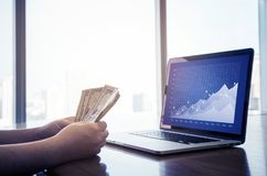 Homem de negócios com dinheiro e portátil da conta Pena, eyeglasses e gráficos fotografia de stock royalty free