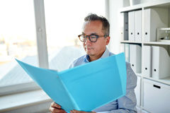 Homem de negócios com dobrador e papéis no escritório fotos de stock royalty free