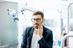 Homem de negócios com dor de dente no escritório dental imagem de stock