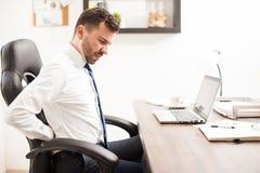 Homem de negócios com dor nas costas no escritório imagem de stock royalty free