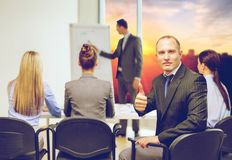 Homem de negócios com a equipe que mostra os polegares acima no escritório foto de stock