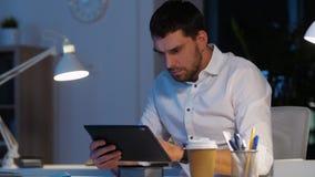 Homem de negócios com funcionamento do PC da tabuleta no escritório da noite video estoque