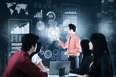Homem de negócios com gráficos virtuais na reunião Fotografia de Stock Royalty Free