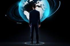 Homem de negócios com holograma do globo da terra sobre o preto Fotografia de Stock