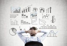 Homem de negócios com mãos atrás da cabeça, infographics Fotografia de Stock