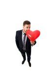 Homem de negócios com o balão dado forma coração Imagens de Stock