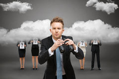 Homem de negócios com o binocular contra o céu tormentoso foto de stock
