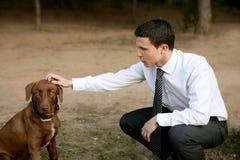 Homem de negócios com o cão ao ar livre no parque Fotografia de Stock Royalty Free