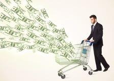 Homem de negócios com o carrinho de compras com notas de dólar Fotografia de Stock Royalty Free