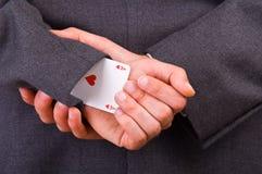Homem de negócios com o cartão do ás escondido sob a luva. Foto de Stock