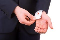 Homem de negócios com o cartão do ás escondido sob a luva. Foto de Stock Royalty Free