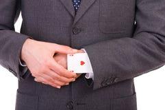 Homem de negócios com o cartão do ás escondido sob a luva. Fotos de Stock Royalty Free
