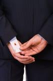 Homem de negócios com o cartão do ás escondido sob a luva. Fotos de Stock