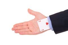 Homem de negócios com o cartão do ás escondido sob a luva. Imagem de Stock