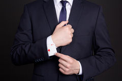 Homem de negócios com o cartão do ás escondido sob a luva Imagem de Stock