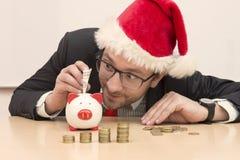 Homem de negócios com o chapéu de Santa Claus que introduz uma nota de dólar no mealheiro Fotografia de Stock
