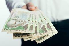 Homem de negócios com o hryvnia em suas mãos Fotografia de Stock Royalty Free