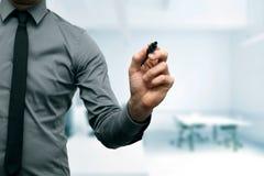 Homem de negócios com o marcador na mão no escritório imagem de stock