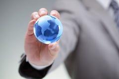 Homem de negócios com o mundo em suas mãos Foto de Stock Royalty Free