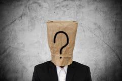 Homem de negócios com o saco de papel marrom na cabeça, com ponto de interrogação, no fundo concreto da textura fotografia de stock royalty free