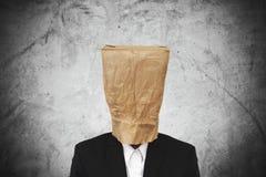 Homem de negócios com o saco de papel marrom na cabeça, no fundo concreto escuro da textura fotos de stock royalty free