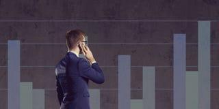 Homem de negócios com o smartphone que está em um backgro do diagrama de coluna Foto de Stock Royalty Free