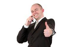Homem de negócios com o telefone de pilha que levanta com polegares acima Fotografia de Stock