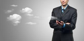 Homem de negócios com o telefone de tela do toque e as nuvens Fotografia de Stock Royalty Free