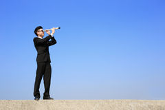 Homem de negócios com o telescópio que olha para a frente Imagens de Stock Royalty Free