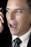 Homem de negócios com olhar nervoso ao telefone de pilha Foto de Stock Royalty Free