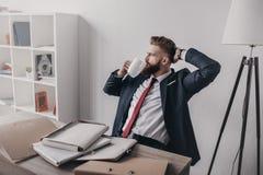 Homem de negócios com originais e dobradores que bebe o café e que senta-se na tabela no escritório Fotografia de Stock Royalty Free