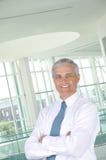 Homem de negócios com os braços dobrados no ajuste do escritório Fotos de Stock Royalty Free