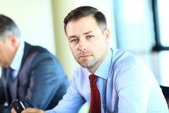 Homem de negócios com os colegas no fundo imagens de stock