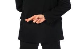 Homem de negócios com os dedos cruzados atrás de seu para trás Fotografia de Stock Royalty Free