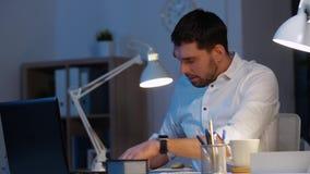 Homem de negócios com papéis e café no escritório da noite vídeos de arquivo