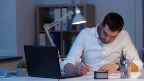 Homem de negócios com papéis e portátil no escritório da noite video estoque