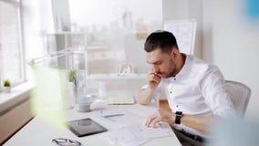 Homem de negócios com papéis e smartphone no escritório vídeos de arquivo