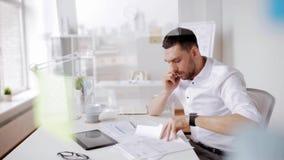 Homem de negócios com papéis e smartphone no escritório filme