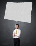 Homem de negócios com papel vazio da brochura Foto de Stock