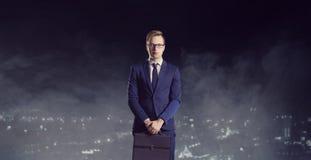 Homem de negócios com a pasta que está em um fundo da cidade da noite Fotografia de Stock