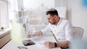 Homem de negócios com PC e papéis da tabuleta no escritório vídeos de arquivo
