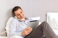 Homem de negócios com PC e telefone da tabuleta na sala de hotel Imagens de Stock
