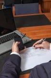 Homem de negócios com pena, originais, portátil e smartphone Fotografia de Stock