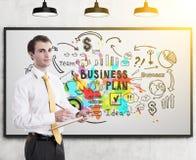Homem de negócios com plano de negócios colorido prancheta Imagem de Stock