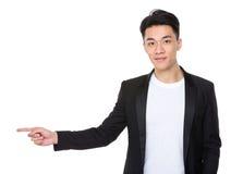 Homem de negócios com ponto do dedo de lado Foto de Stock