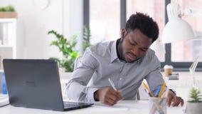 Homem de negócios com portátil e papéis no escritório vídeos de arquivo