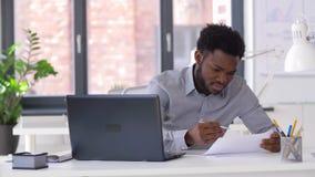 Homem de negócios com portátil e papéis no escritório filme